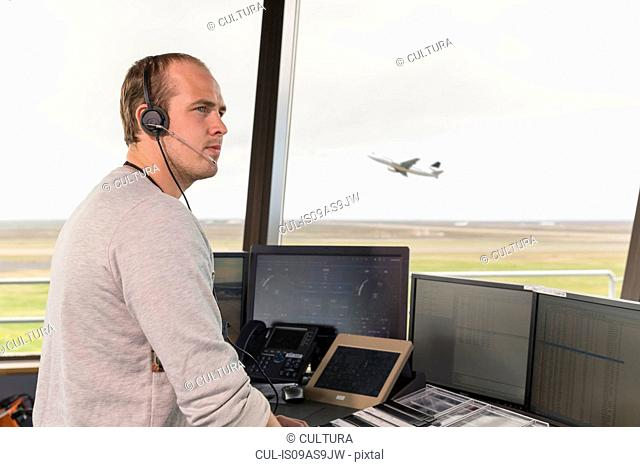 Side view of young man in air traffic control tower, looking away, airplane taking off behind