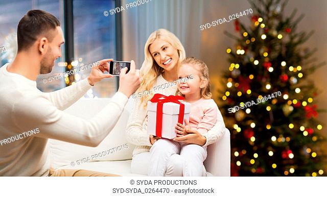 man taking picture of his family on christmas