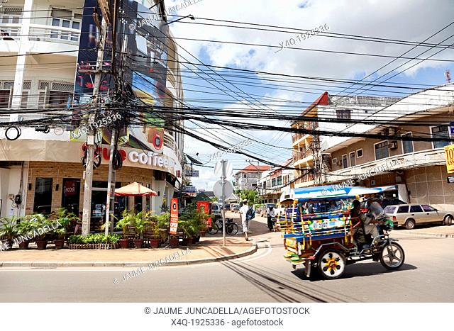 In a tourist street of Vientiane, a sunny morning in the monsoon season a tourist's tuk tuk across at full speed