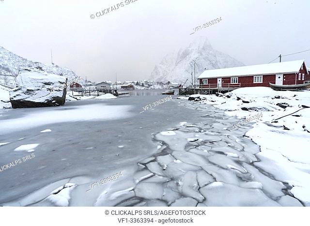 Frozen fjord with red cabin and Olstinden peak in the background. Reine, Nordland, Northern Norway, Norway