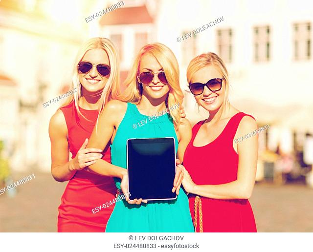 holidays and tourism concept - beautiful blonde girls toursits showing tablet pc with blank screen in the city