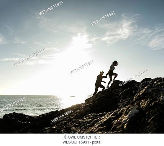France, Brittany, young couple climbing on a rock at the beach at sunset