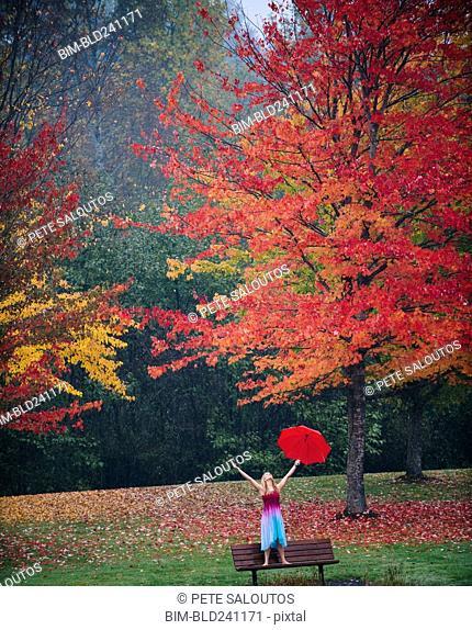Caucasian woman holding umbrella in rain on park bench