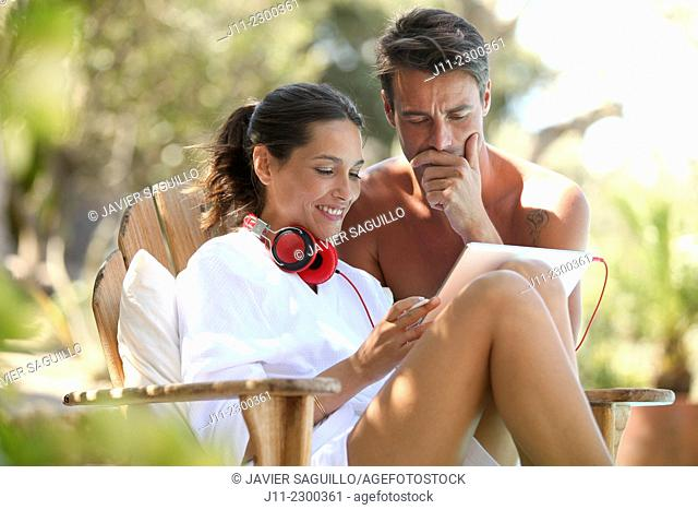 Couple, digital tablet and headphones