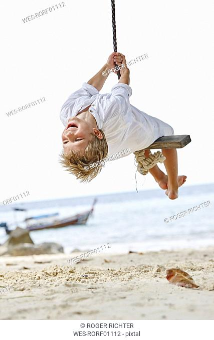 Thailand, Phi Phi Islands, Ko Phi Phi, happy boy on a rope swing on the beach