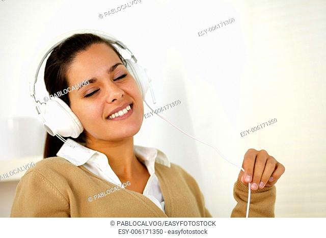Portrait of a relaxed young woman with headphone listening music