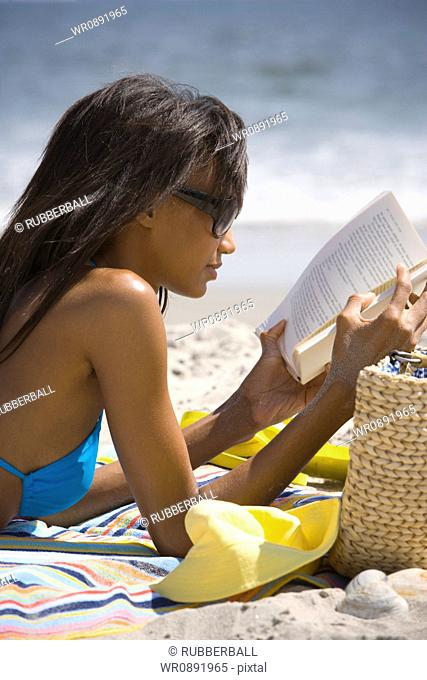 Profile of a young woman reading on the beach