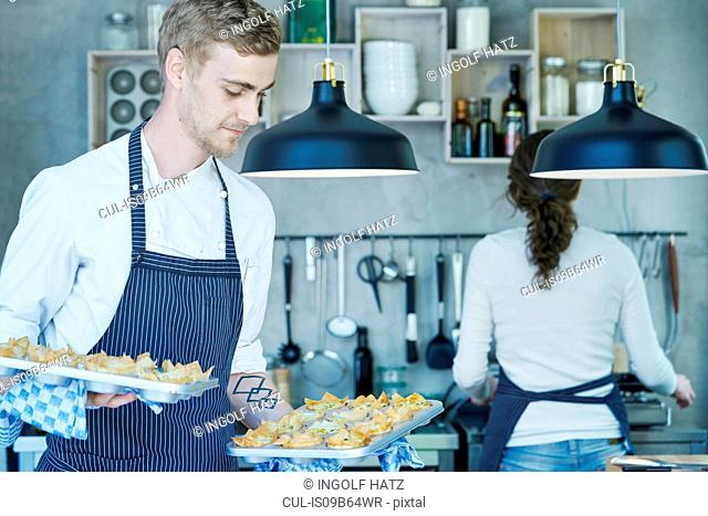 Chef in kitchen, holding baking trays of canapes
