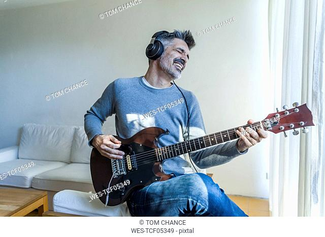 Mature man at home playing electric guitar and wearing headphones