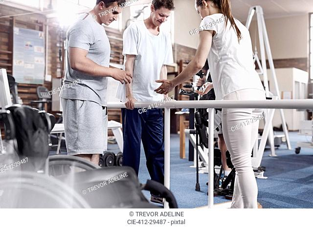 Physical therapists helping man walk