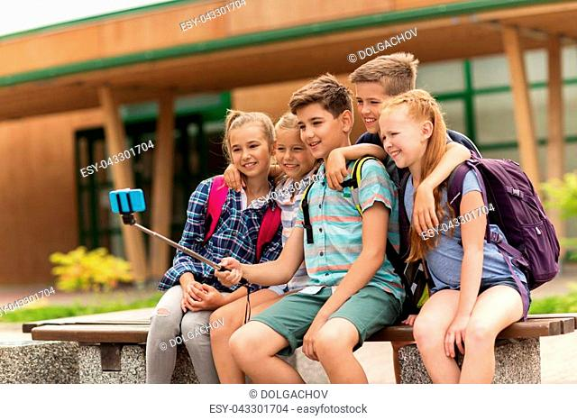 primary education, technology, friendship, childhood and people concept - group of elementary school students with backpacks sitting on bench taking picture by...