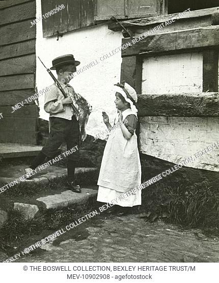 Black and white. Young boy with gun and dead duck standing on steps in front of young girl. Part of Box 102, Nursery Rhymes