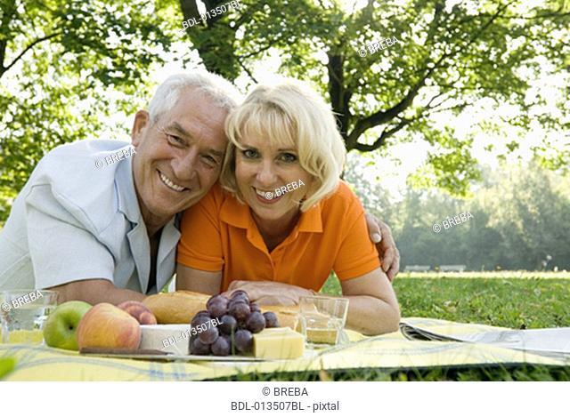 portrait of happy couple having picnic in park