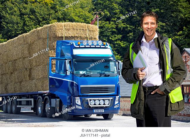 Man Standing By Weighbridge As Lorry Transports Straw Bales