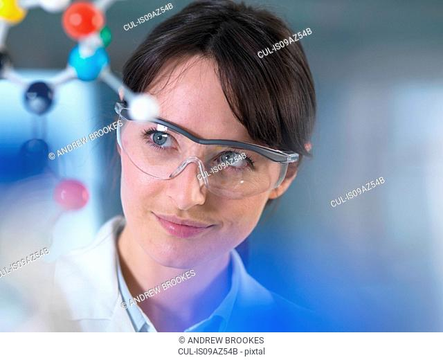 Scientist analysing molecular model in laboratory