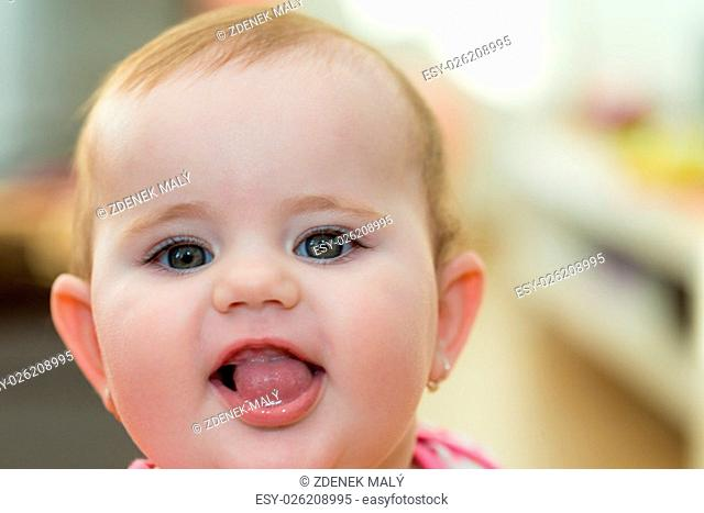 Happy cute little one year old girl indoor smiling and stick your tongue
