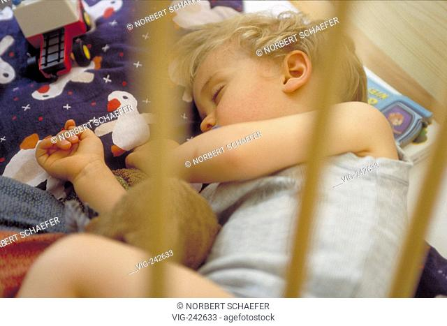 portrait, indoor, 2-year-old blond boy wearing underwear sleeps with his toys in a bed with wooden bars  - GERMANY, 26/02/2005