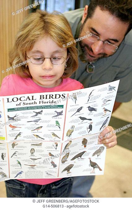 Girl, lazy eye, father, bird identification information. Ernest Coe Visitors Center. National Everglades Park. Florida. USA
