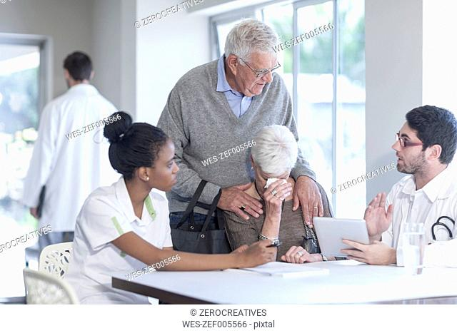 Crying senior woman with husband at clinic talking to doctor and nurse