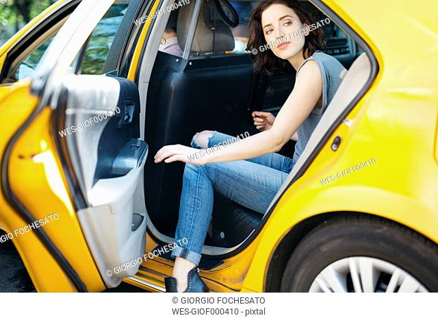 USA, New York City, portrait of young woman getting on a yellow cab