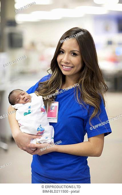 Nurse holding newborn baby in hospital