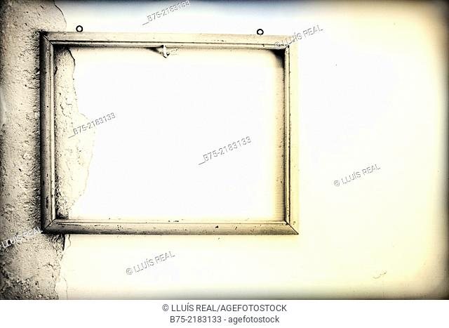 Old empty frame hanging on a white wall