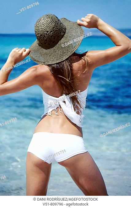 Back view of a woman with a hat by the sea