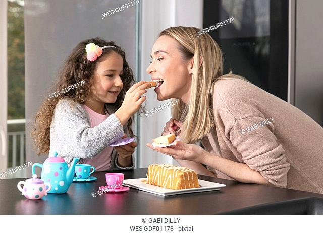 Mother and little daughter little playing together with doll's china set