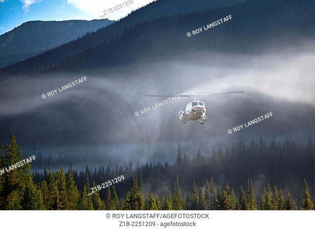 Downdraft from a helicopter rotor is evident in early morning mist