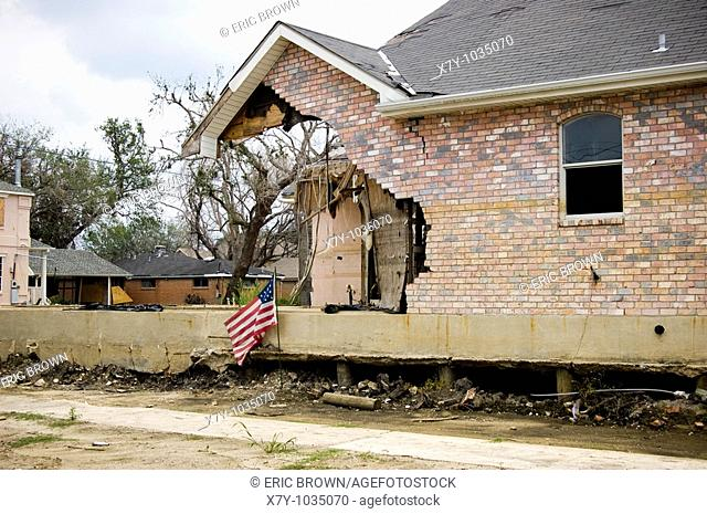 An American flag sits outside a damaged home in the Lake District of New Orleans, LA