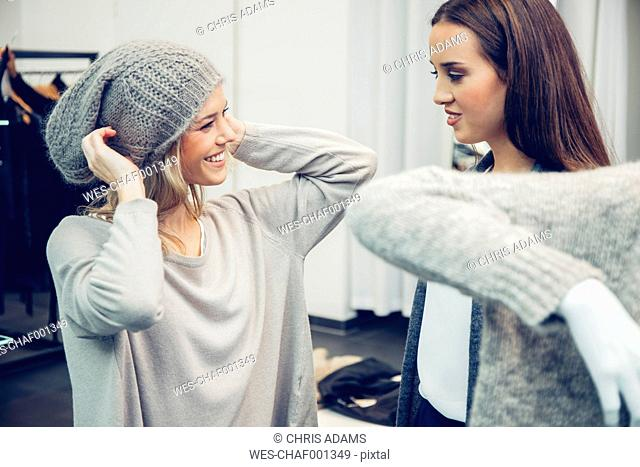Young woman assisted by friend putting on woolly hat in a boutique