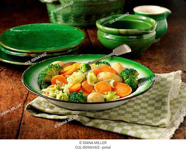 Sliced carrots, broccoli, cabbage and potatoes in ornate green serving dish