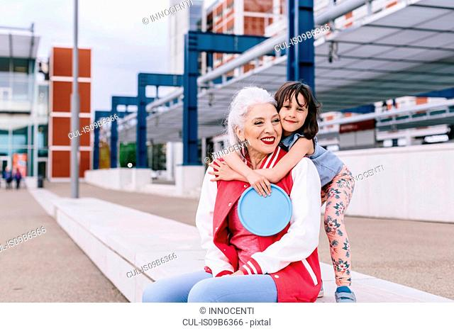Portrait of girl hugging mature woman sitting on wall in city