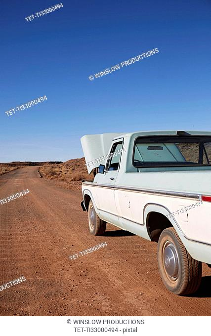 USA, Arizona, Broken pick up truck parked on desert road