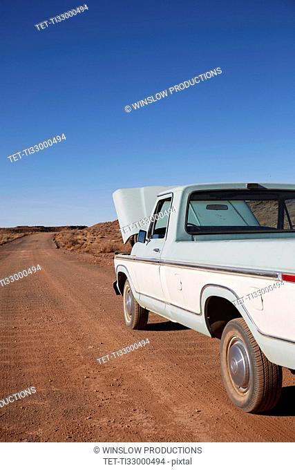 USA, Arizona, Broken pick up truck parked on desert road