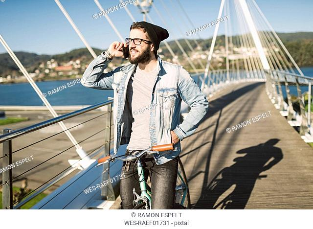 Young man with fixie bike on a bridge on the phone