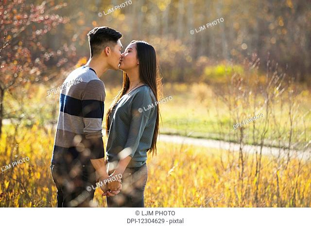 A young Asian couple enjoying a romantic time together outdoors in a park in autumn and kissing each other in the warmth of the sunlight during the early...