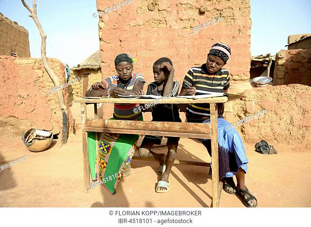 Teenage girls, 14 and 17 years, and boy, 9 years, doing homework, village Koungo, Plateau Central, Burkina Faso