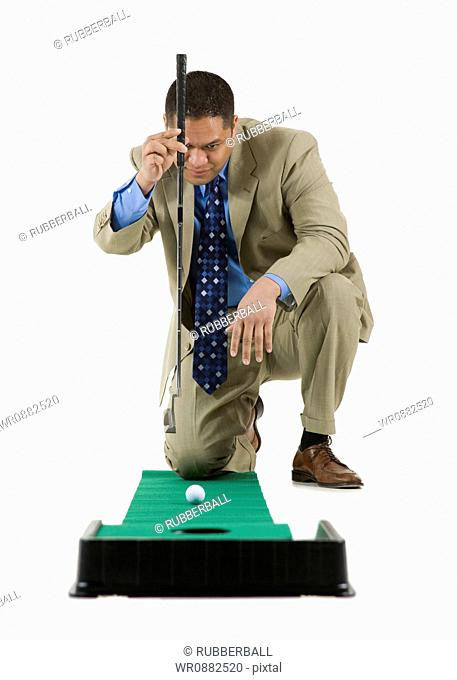 Businessman playing golf on artificial turf