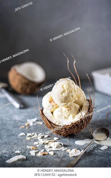 Coconut ice cream scoops in a halved coconut with coconut chips