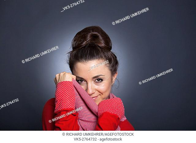 A beautyful women with dark hair is hiding her face with red pullover