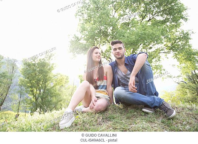 Portrait of young couple sitting on grass, Piemonte, Italy