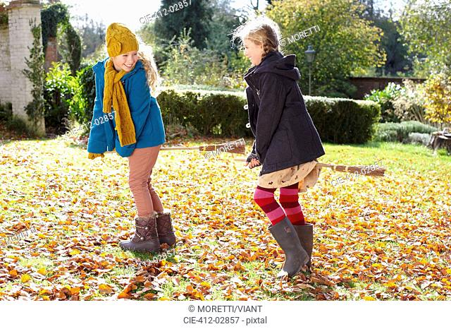 Girls playing together in autumn leaves