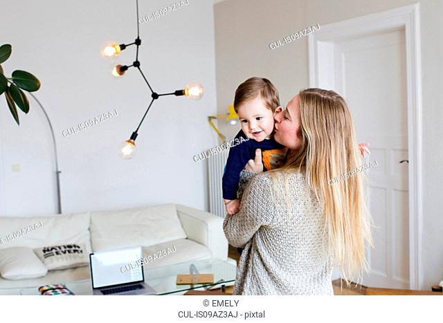 Mid adult woman kissing baby son on cheek in living room