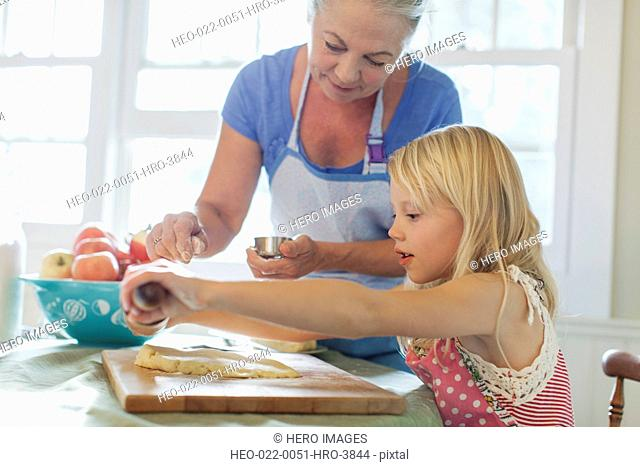 Grandmother assisting granddaughter with rolling pin