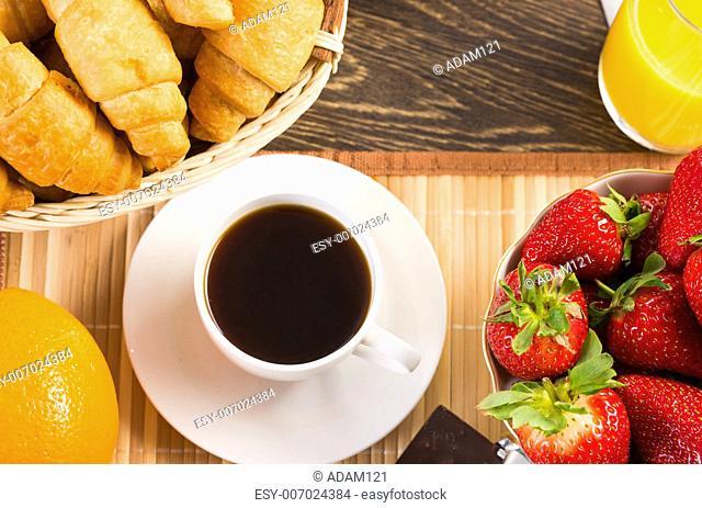 early breakfast, orange juice, croissants and strawberries