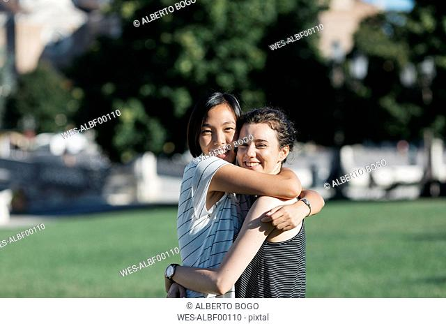 Portrait of two best friends hugging each other in the park