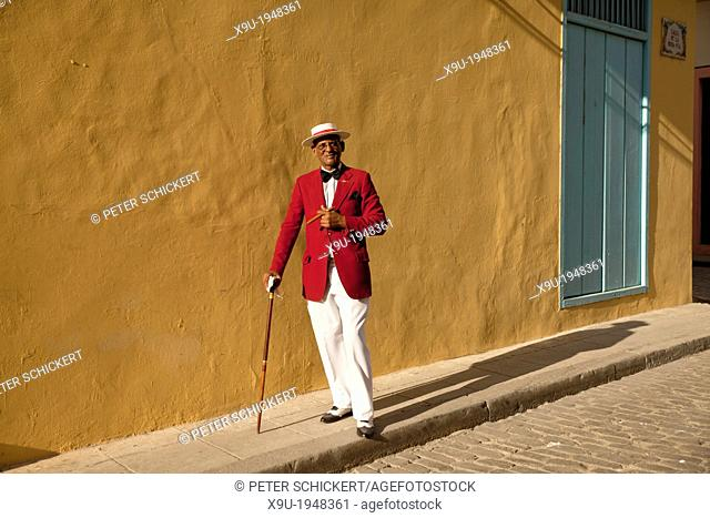 the actor Pedro Pablo Perez with red suit, hat and cigar in Havana, Cuba, Caribbean