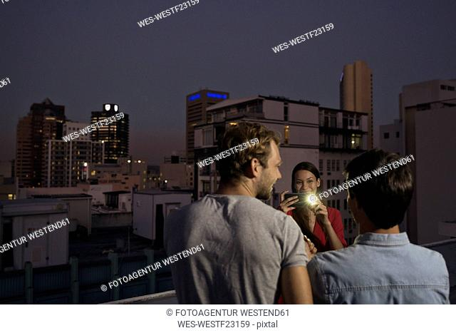 Young woman taking pictures of friends at a rooftop party