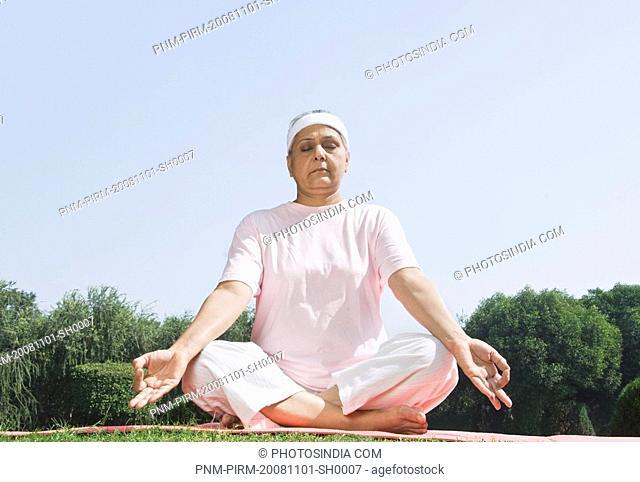 Woman practicing yoga in a park, New Delhi, India